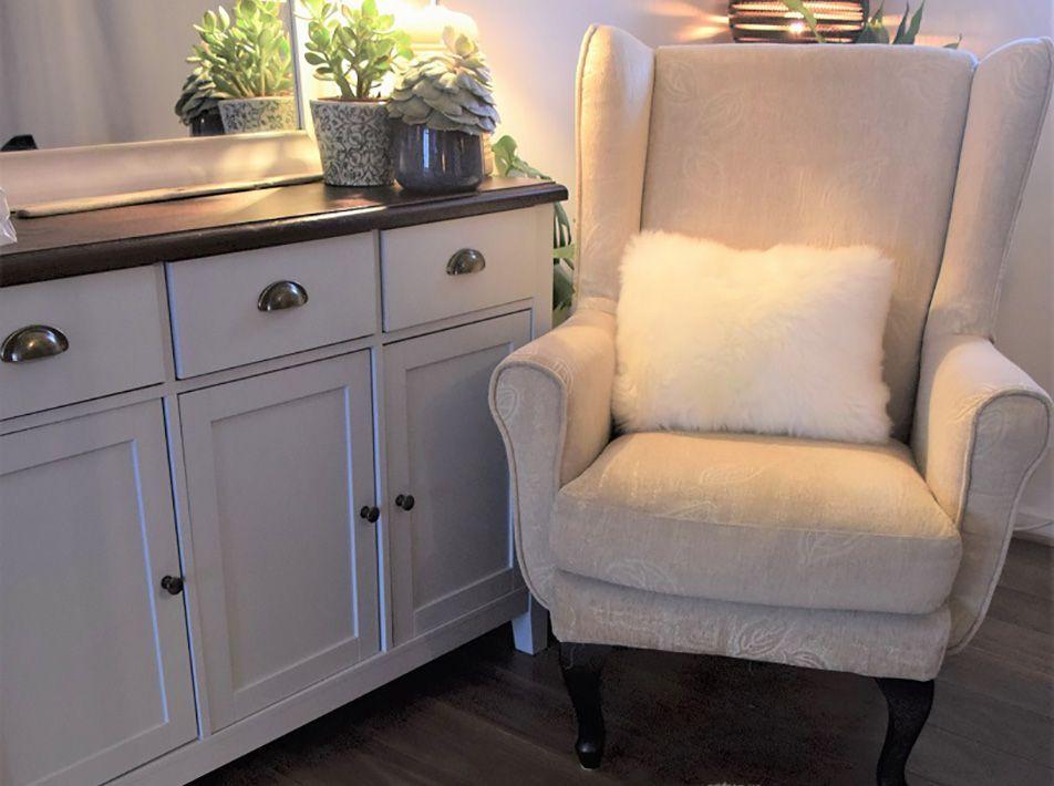 Oblong sheepskin cushion on chair